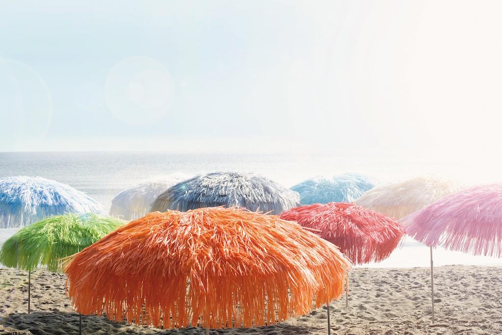 Mobiles Outdooraccessoires Sonnenschirm. Viele verschiedenfarbige Sonnenschirme am Strand