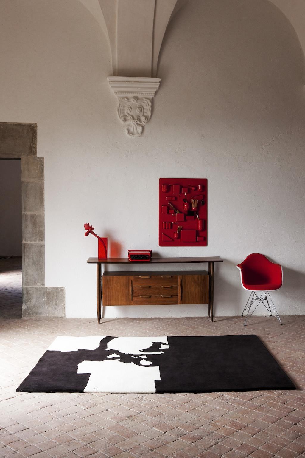 Nanimarquina Chillida Teppich vor Teak Sideboard, Uten.Silo in Rot an der Wand und roter Eames Plastic Chair DAW Vollpolster