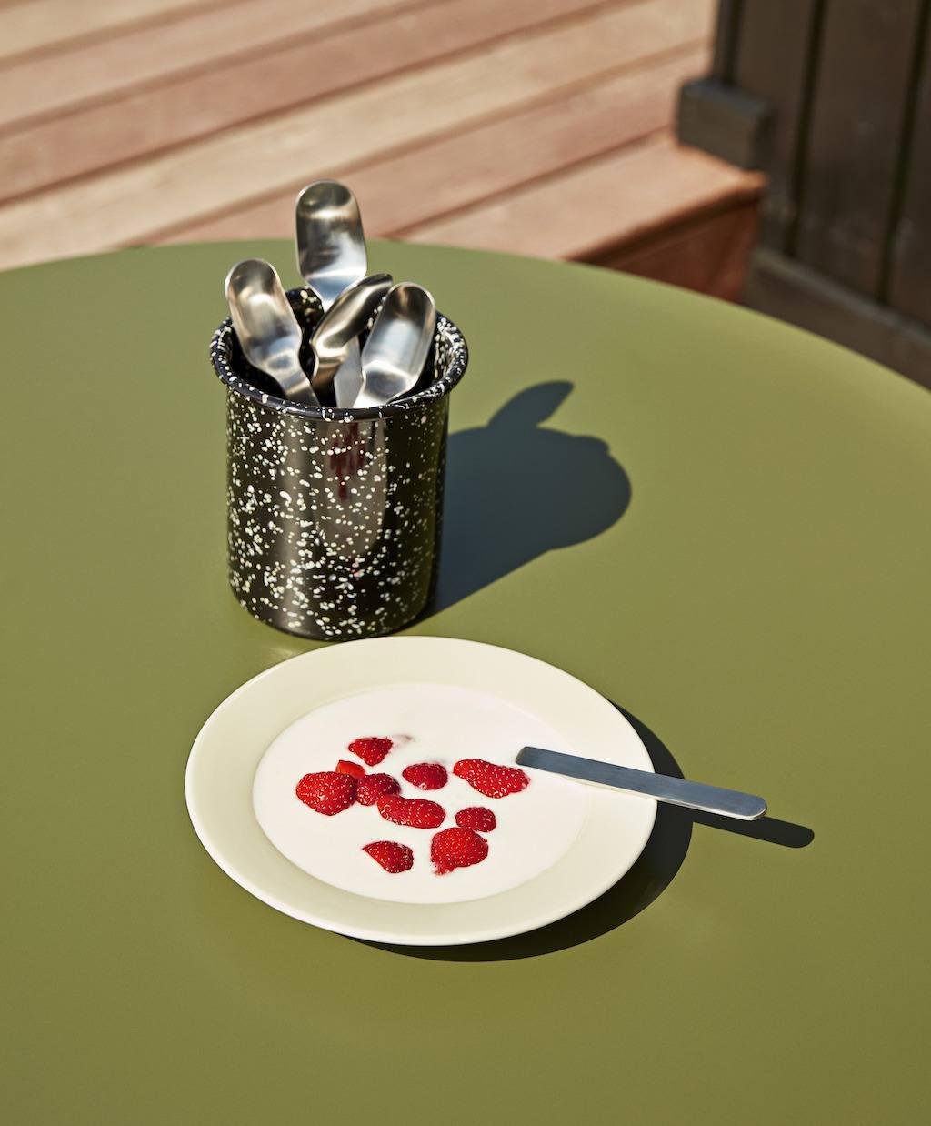 Emaillebecher mit Löffeln und Teller mit Erdbeeren in Sahne