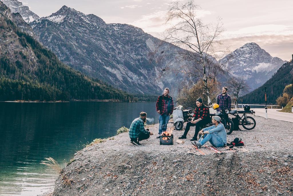 Berge, Bierbox von Höfats, Menschen sitzen um Feuer, mobile Outdoormöbel, Teppich