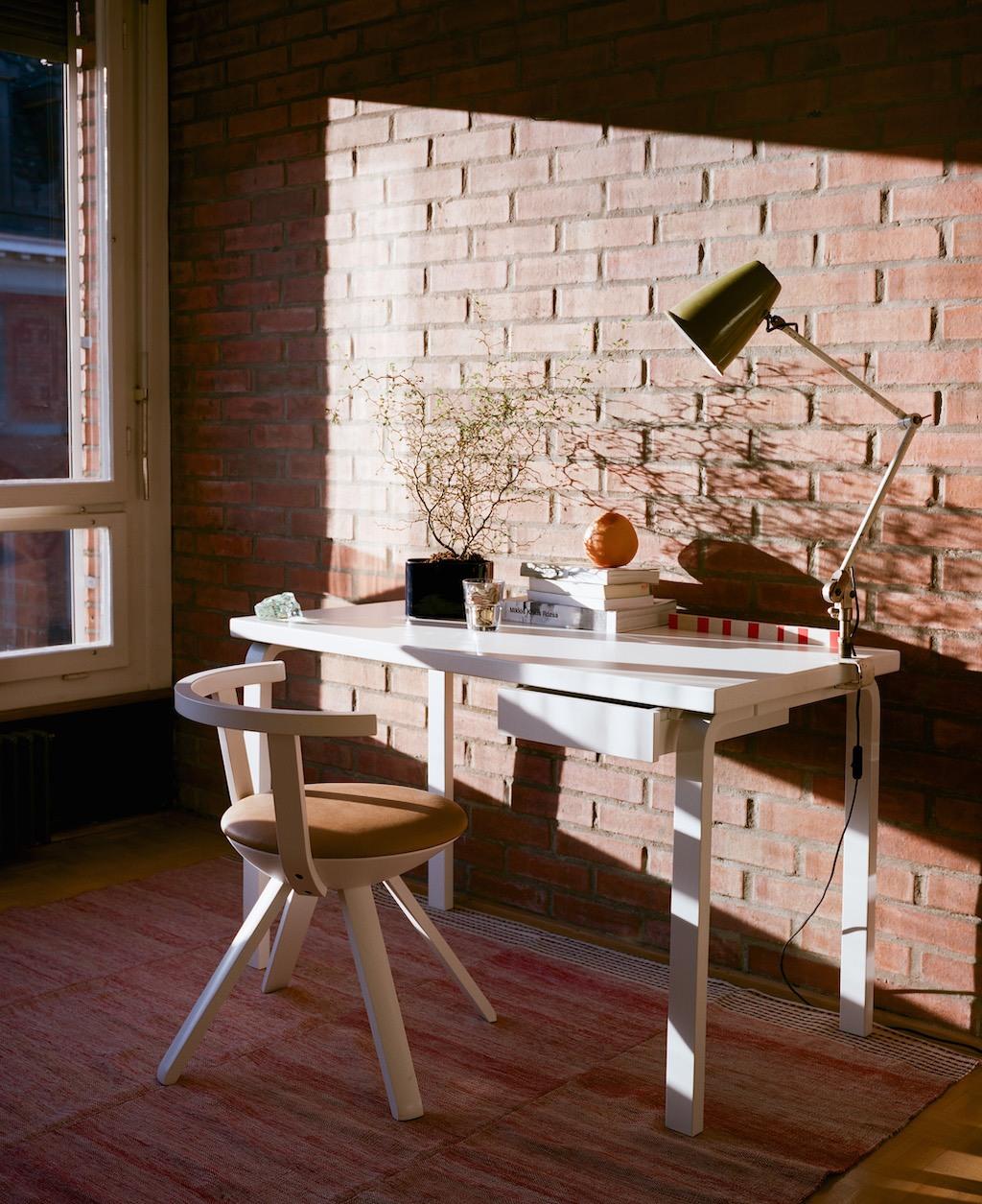 Artek Schreibtisch, Stuhl und Leuchte, unverputzte Ziegelsteinwand, zarte Zimmerpflanze