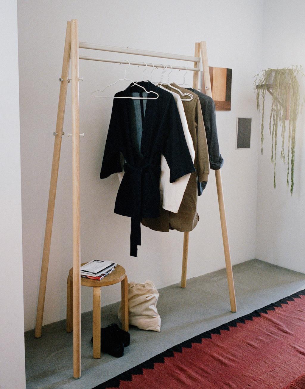 Kleiderstange aus Holz mit Bekleidung und Bügeln für die erste eigene Wohnung