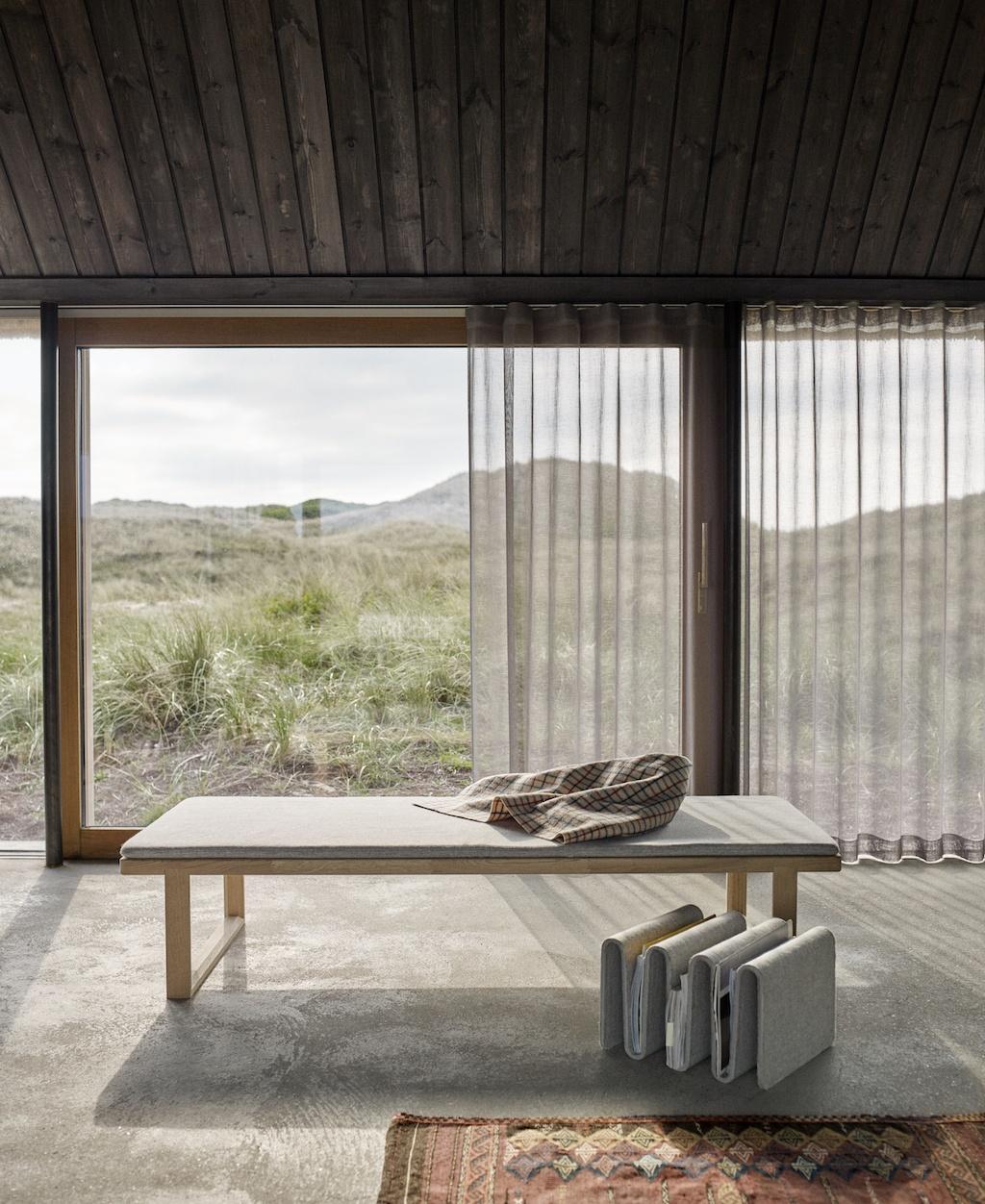 Salon Solist par excellence: ein Tagesbett vor einer großen Front aus bodentiefen Fenstern mit Blick auf eine grüne Landschaft.