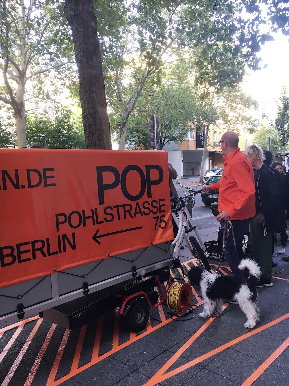 Niels Holger Moormann mit Hund steht vor dem POP HUB Anhänger und erklärt das Fahrzeug.