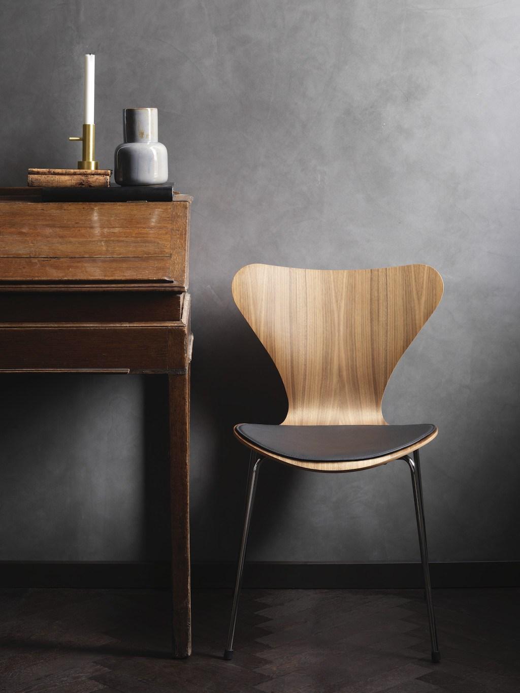 Solitär und Salon Möbel: ein alter Sekretär und ein Serie 7 Chair von Fritz Hansen vor einer dunkelgrauen Wand.