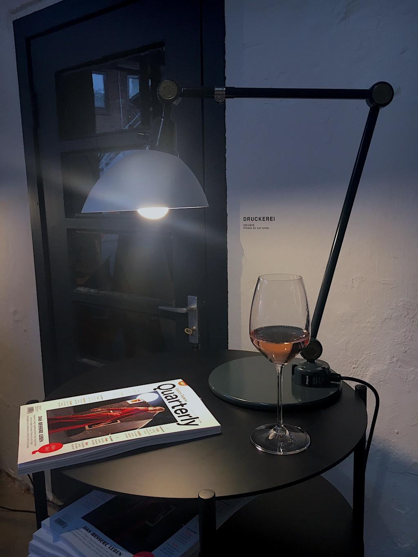 Tisch mit Tischleuchte und halbvollem Weinglas bei Midgard 100 in Hamburg.