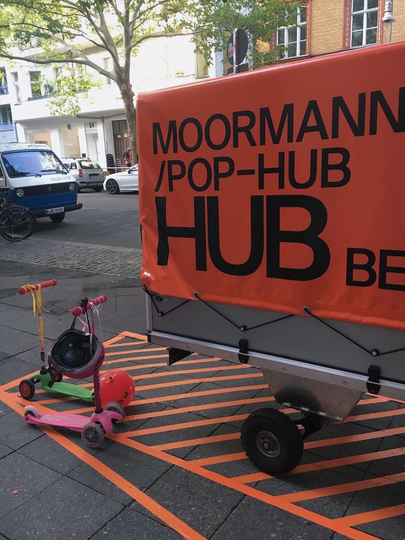 Zwei bunte Kinderroller stehen geparkt neben dem POP HUB Sattelschlepper.