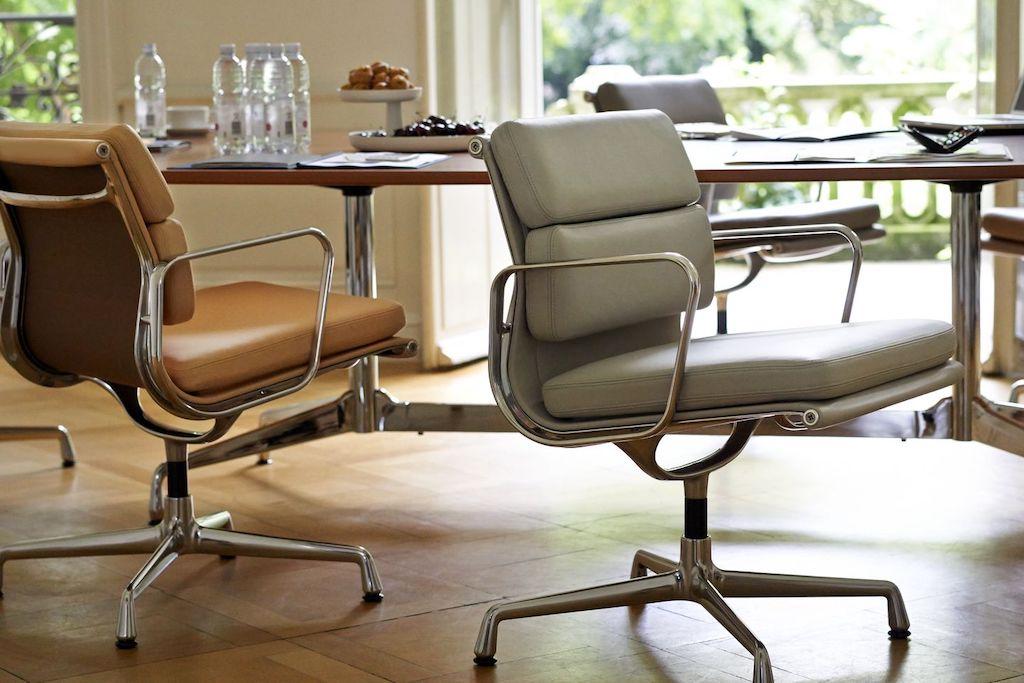 Zwei Soft Pad Chairs im Vordergrund. Einer Sandfarben, der andere in warmem Cognag-Ton. Auch ihr Design trägt die DNA der Aluminium Group