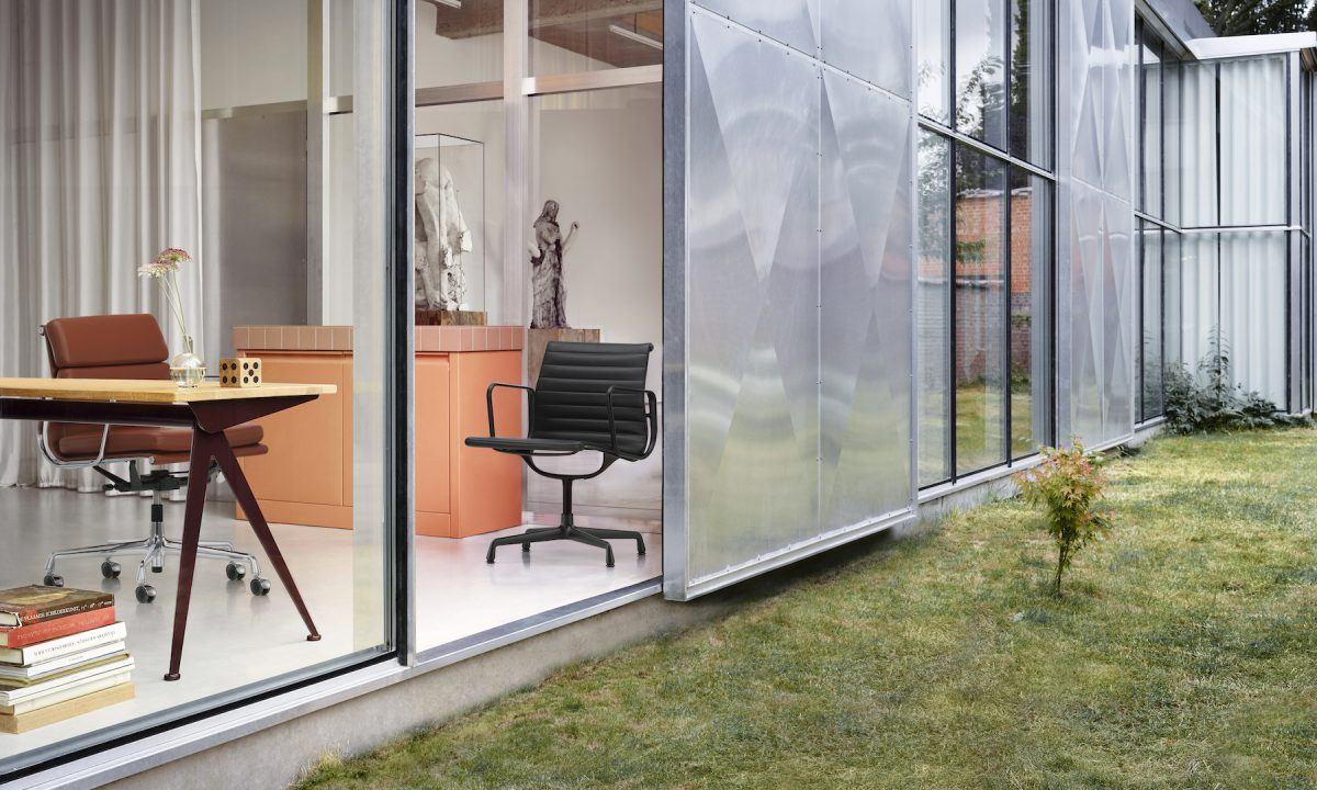 Blick von Außen nach drinnen, Schreibtisch und daran ein Soft Pad Office Chair in sattbraunem Leder. In der Ecke ein Eames Aluminium Chair in All Black.