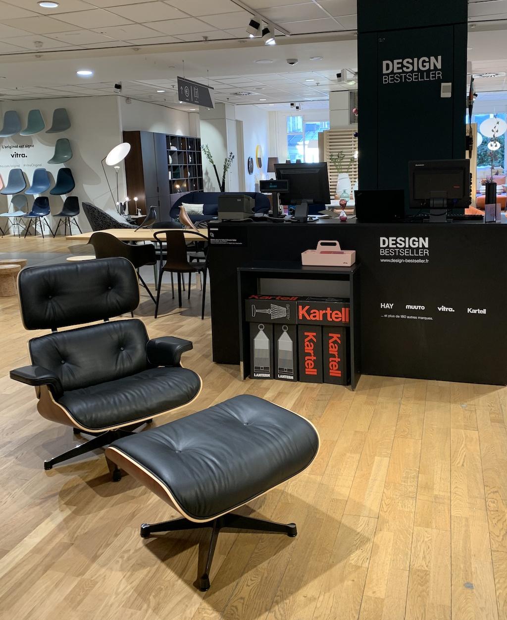 Lounge Chair und Ottomane von Vitra in schwarzem Leder vor schranzem Kassentresen