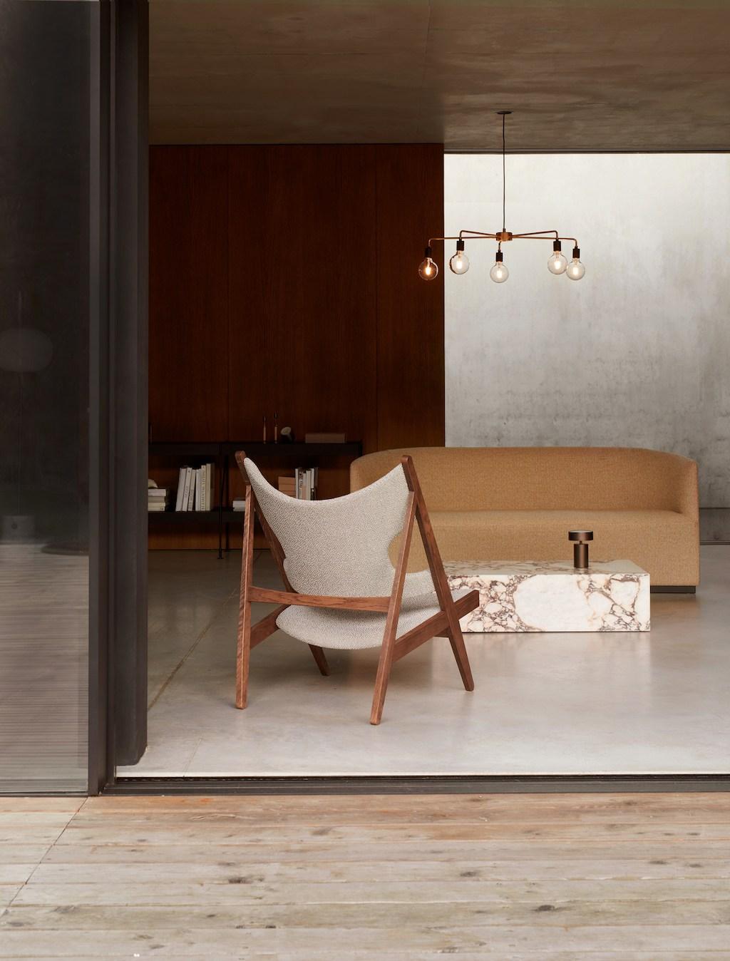 Blick von Terrasse nach drinnen auf Knitting Chair und Tearoom Sofa von Menu. Polierter Betonboden, Zwischenwand aus Teakpanelen.
