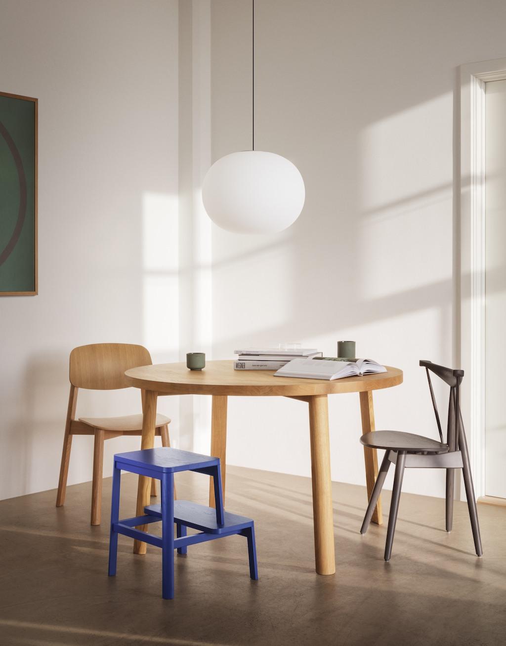 Salon Solisten am Esstisch. Ein runder Tisch aus hellem Holz, daran stehen zwei Stühle und ein blauer Hocker.