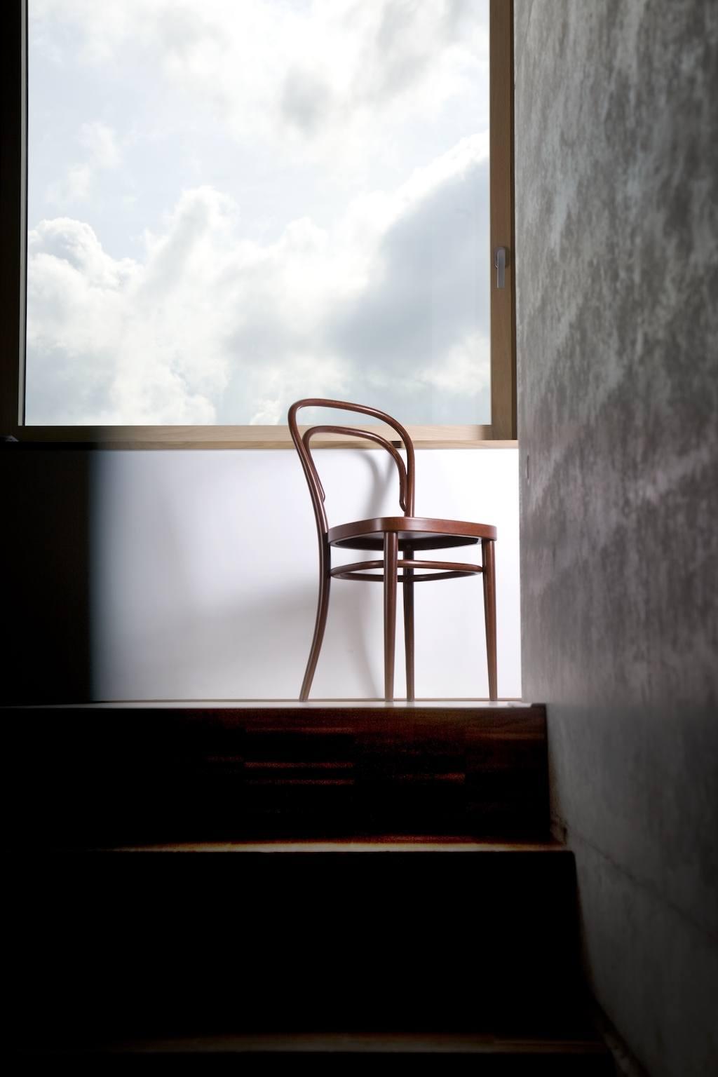 Thonet 214 Stuhl steht am oberen Treppenabsatz vor einem großen Fenster. Im Hintergrund Wolken.