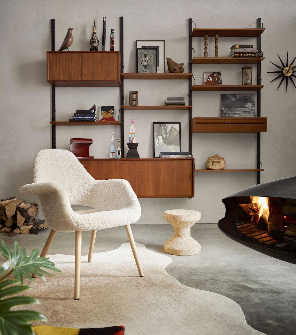 Stuhl mit Schaffellbezug von Vitra steht vor einem Wandregalsystem in Kirsch- oder Nussbaumholz. Ein Feuer brennt im Kamin.