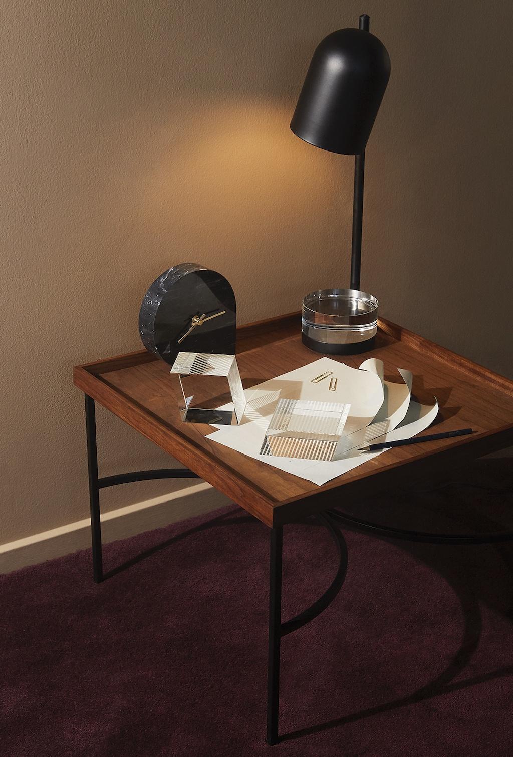 Die neuen Leuchten - Luceo Tischleuchte von AYTM in schwarz steht auf kleinem Beistelltisch