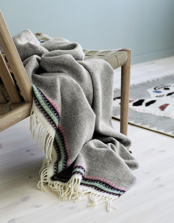 Decke aus grauer Schurwolle hängt von einem Sessel herunter.