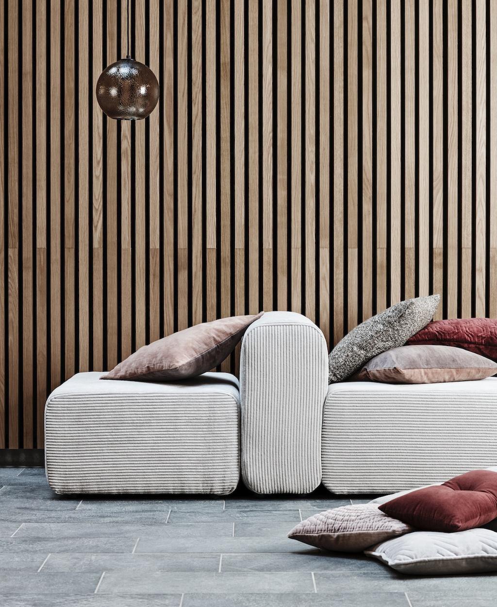 Modulares Sofa vor einer Hand aus Holzlamellen. Darauf und davor liegen Kissen und Rot- und Grautönen. Textilien als Dekotipps für den Herbst.