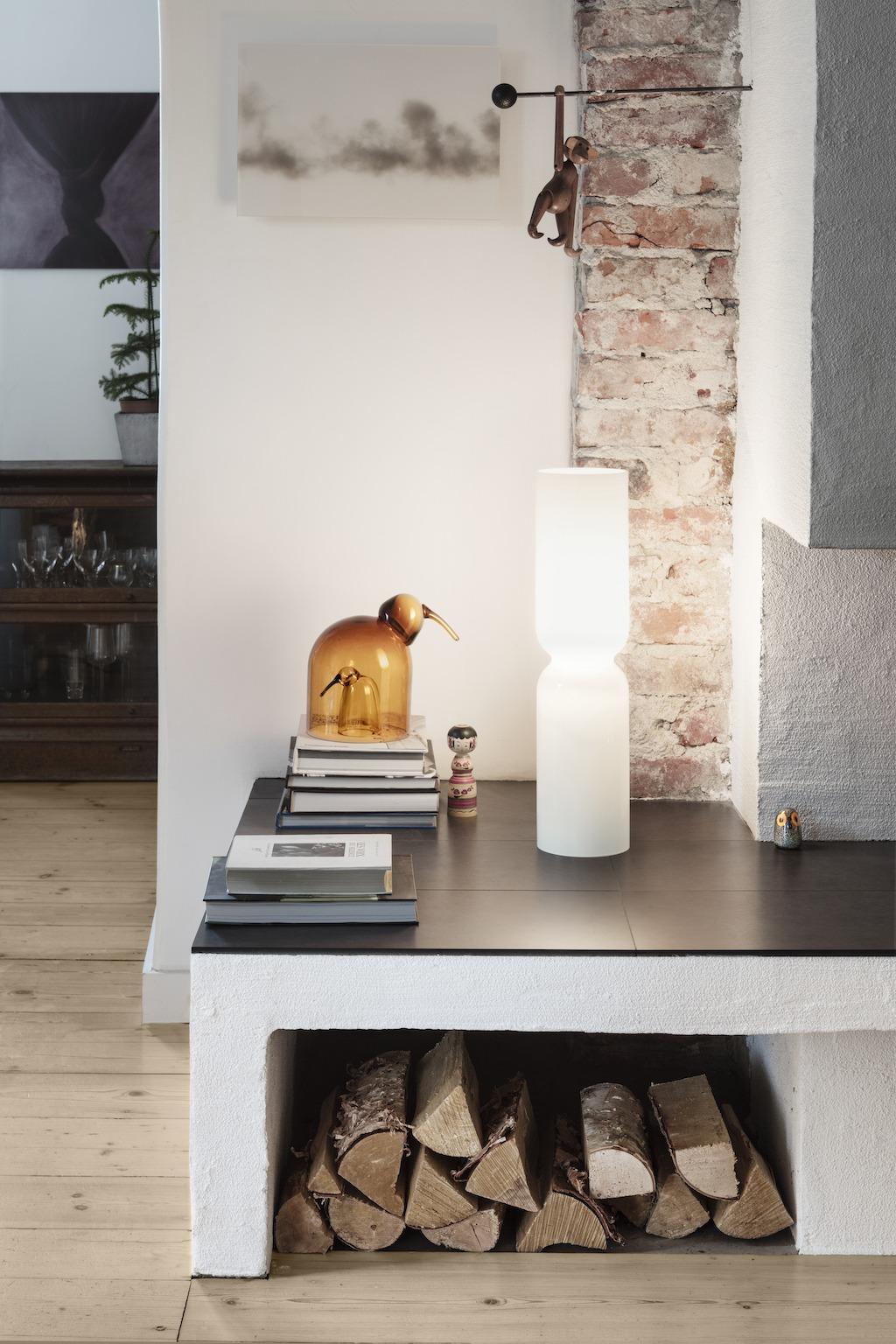 Holzscheite unter der Ofenbank, darüber steht eine kerzenförmige Leuchte in weiß, einige Bücher und kleine Dekoobjekte. Dekoideen für den Herbst.
