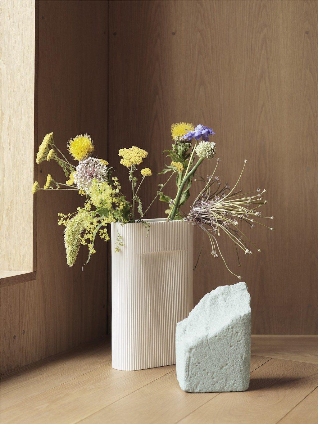 Ridge Vase von Muuto mit frischen Blumen. Davor ein weißer Block, womöglich aus Gips oder Blumensteckmasse.