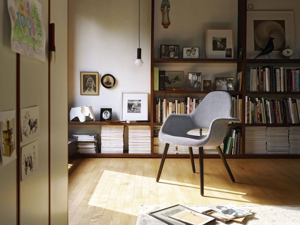 Organic Chair in grauem Hopsak vor einer Regalwand.