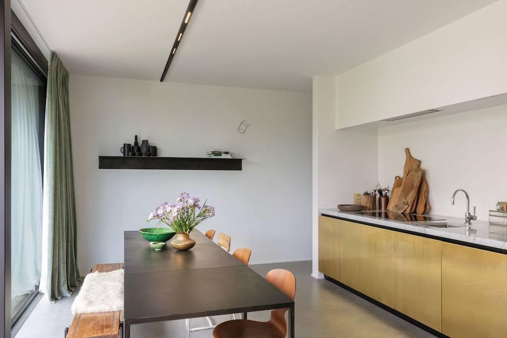 Moderne Kücje mit Messingfronten und langem Tisch mit Holzbank und -Stühlen.