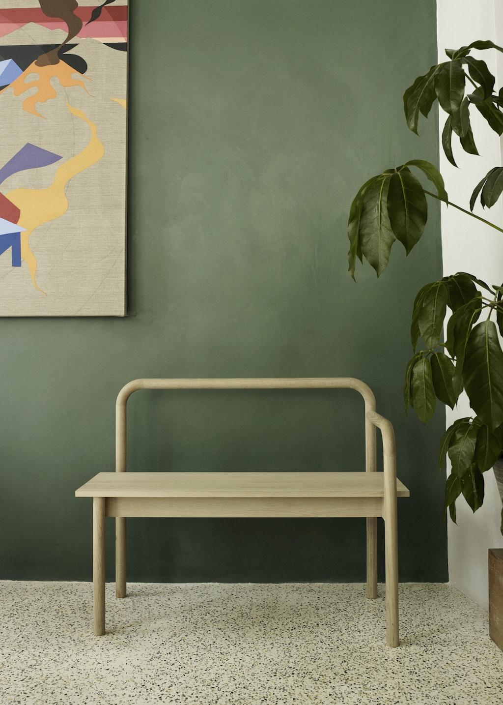 moderne Holzbank vor einer grünen Wand