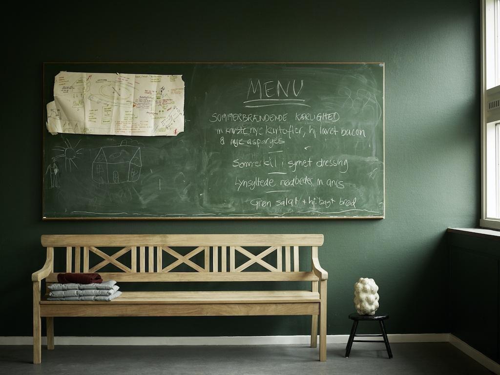 Klassische Holzbank vor einer dunkelgrünen Wand mit einer großen Tafel