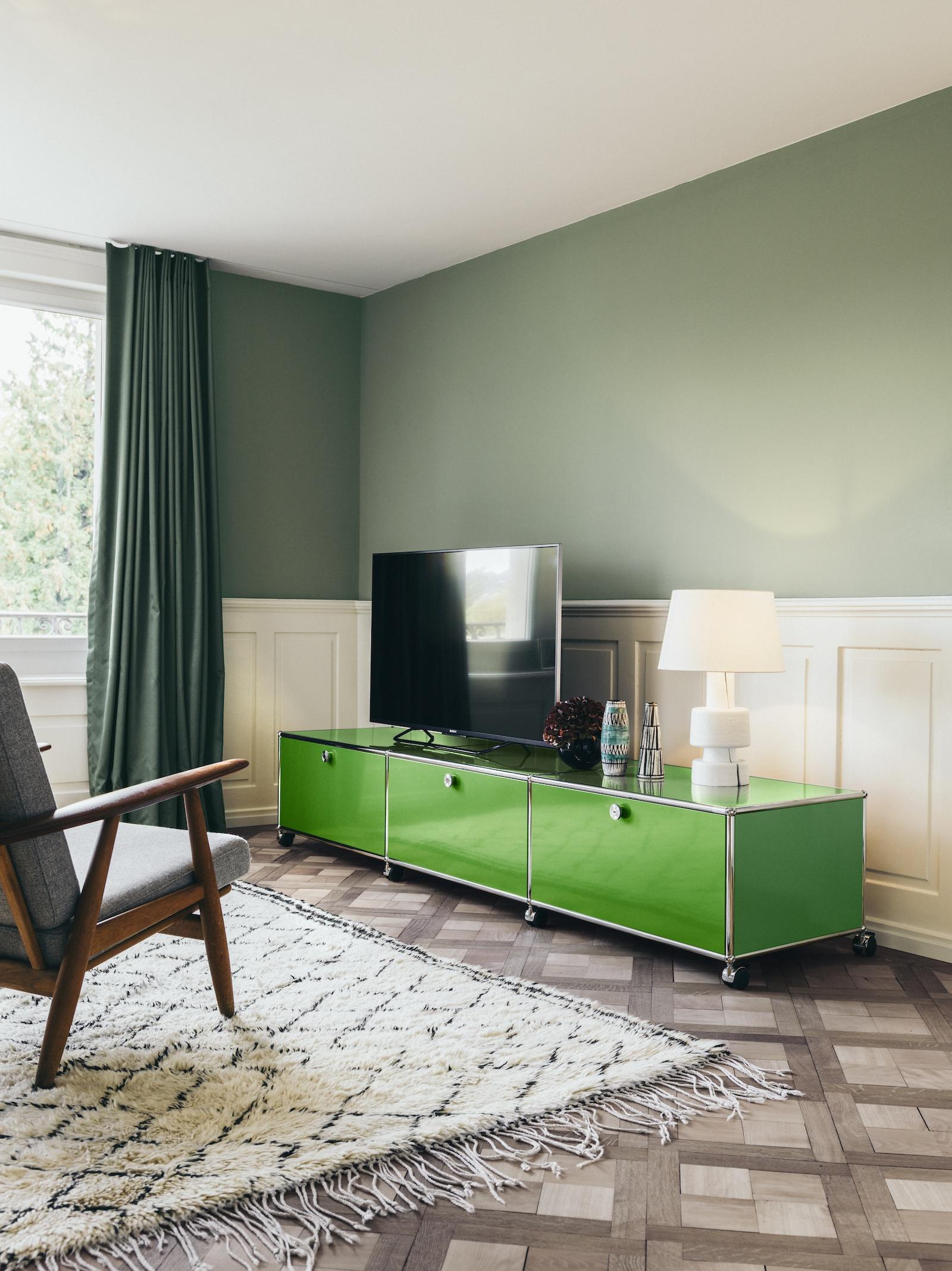 USM Haller Sideboard in Grün als TV Bank. Davor ein Sessel auf einem Beni Ourain Teppich