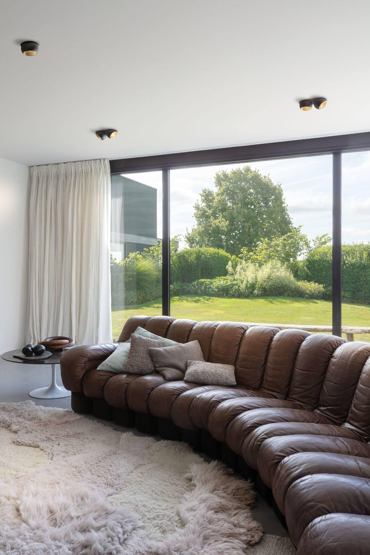 Ledersofa und langflorteppich. Taktile Materialien machen das Wohnen zu einem sinnlichen Erlebnis