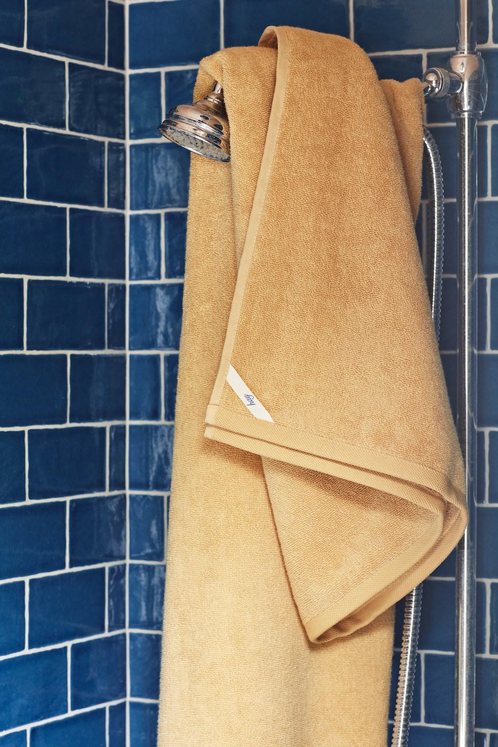 Gelbes Handruch über Duschkopf gehängt. Wände gefliest mit blauen Metrofliesen.