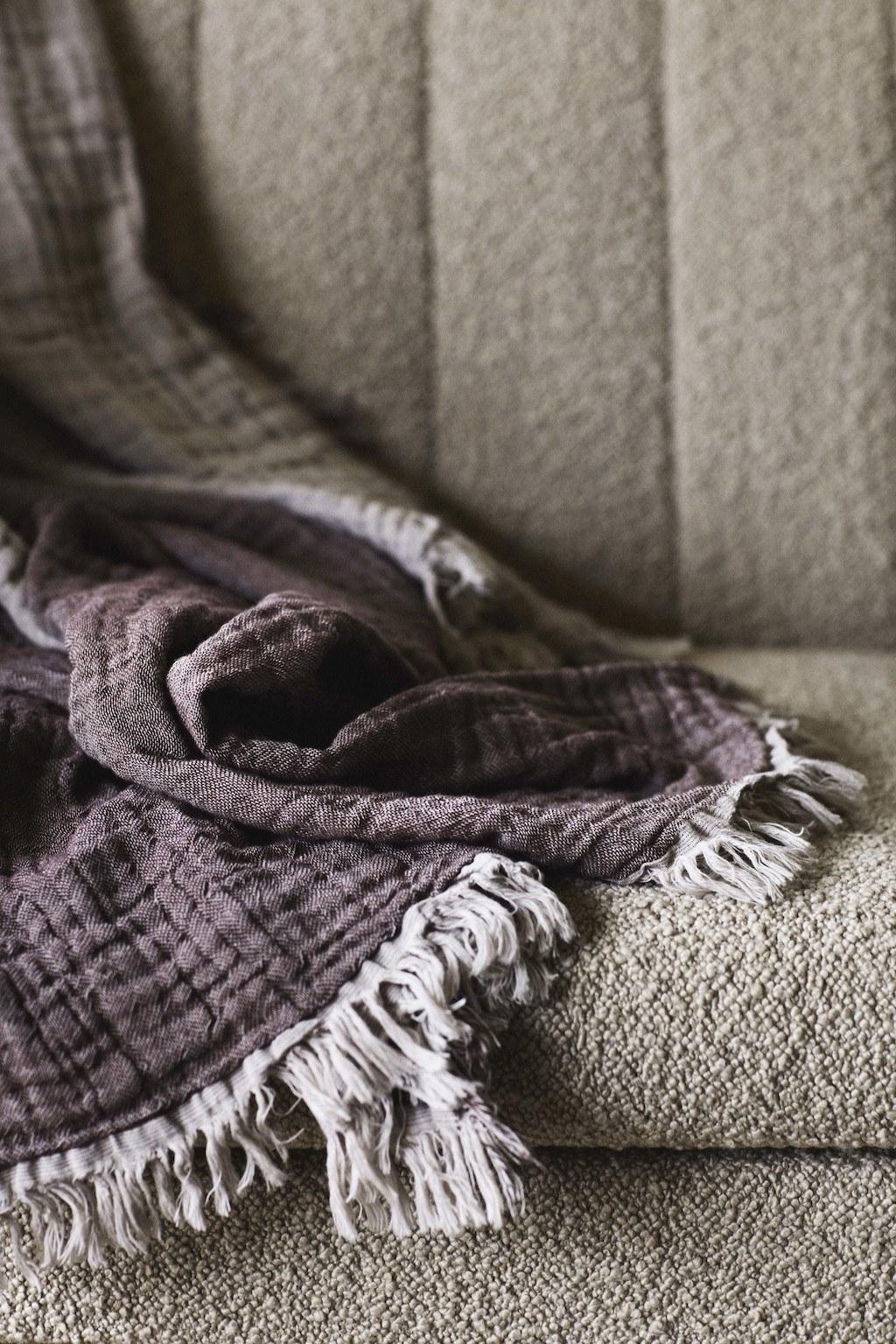 Interieur Materialkunde: 7 spannende Werkstoffe Bouclébezug eines Sofas und drapiertes Plaid