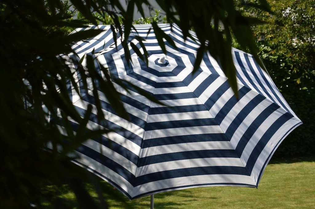 Sonnenschirm in blau-weißem Streifenmuster auf einer Wiese.