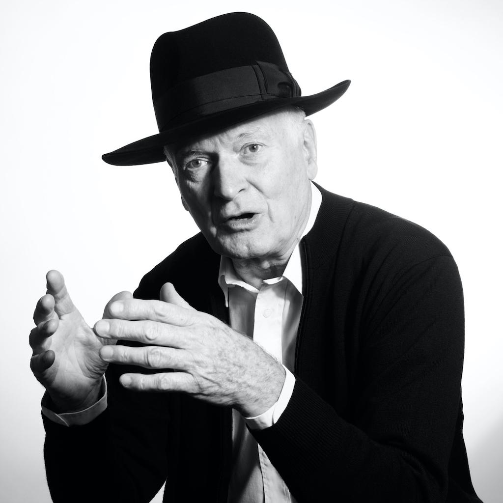 Schwarz-Weiß-Bild. Sir Kenneth Grange gestikulierend mit Hut