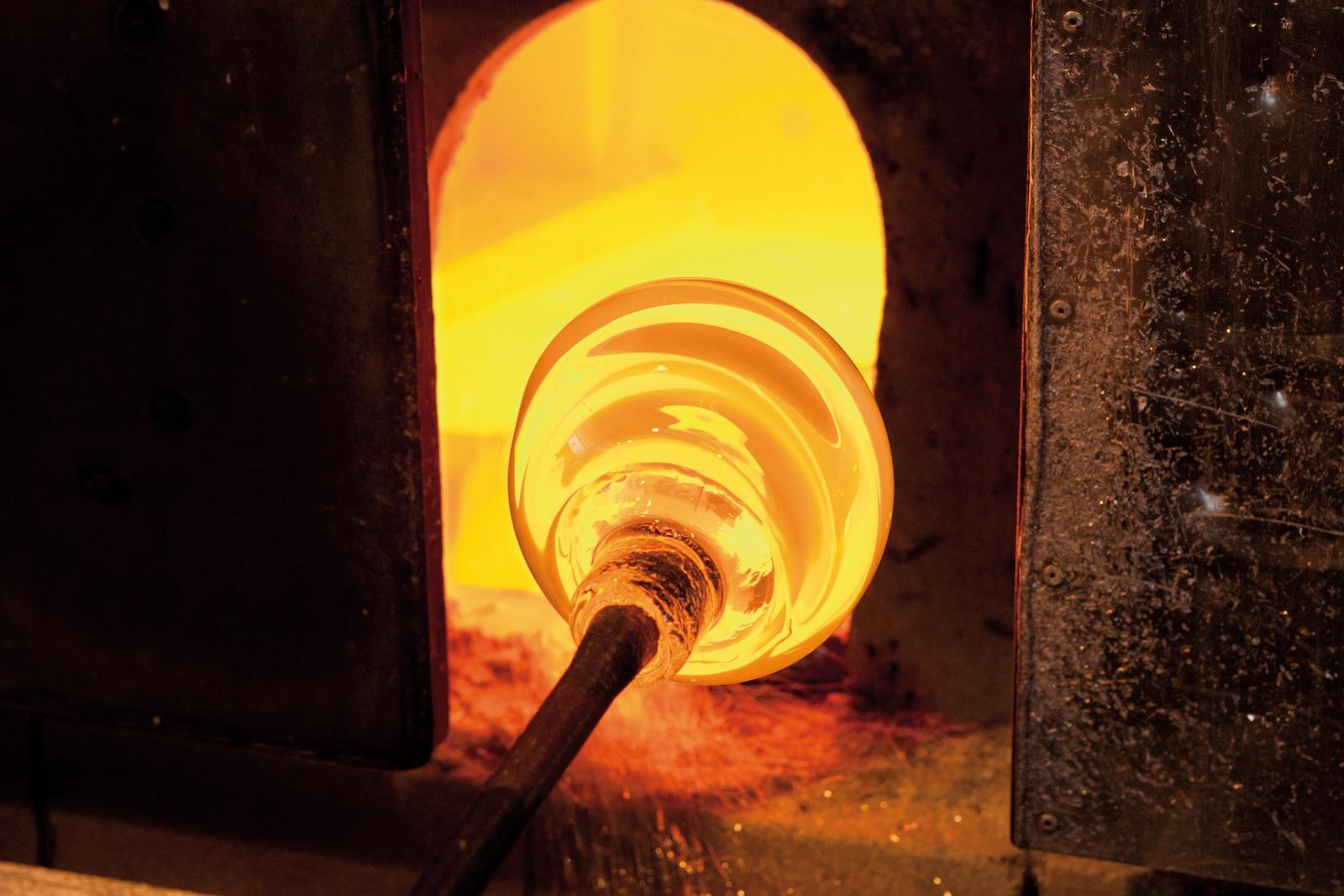 Die Glasmasse wird aus dem Schmelzofen geholt. Anschließend muss der Glaskörper immer wieder zurück in die Hitze, um ihn weiter bearbeiten zu können.