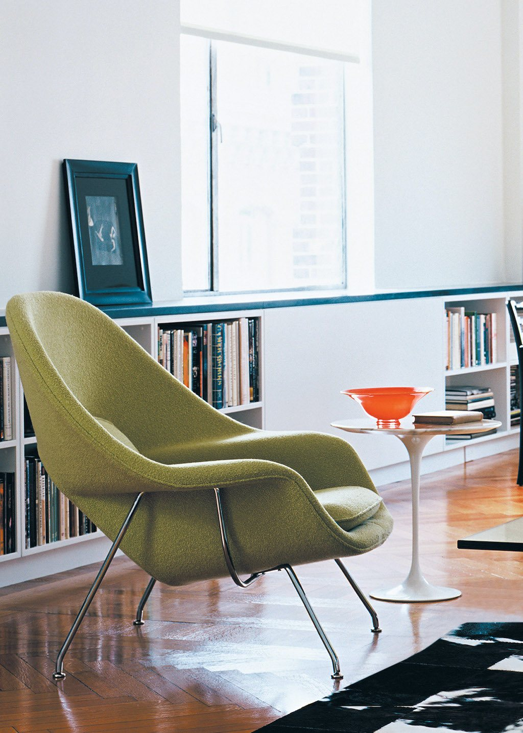 Design als Investition. Womb Chair und Saarinen Table, im Hintergrund ein durchgehendes, hüfthohes Bücherregal.