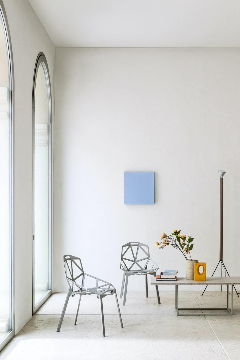Design als Investition: zwei Chair One in grau in einem hohen, weißn Raum. Rechterhand ein Sofatisch mit Büchern und einem blühendem Zweig.