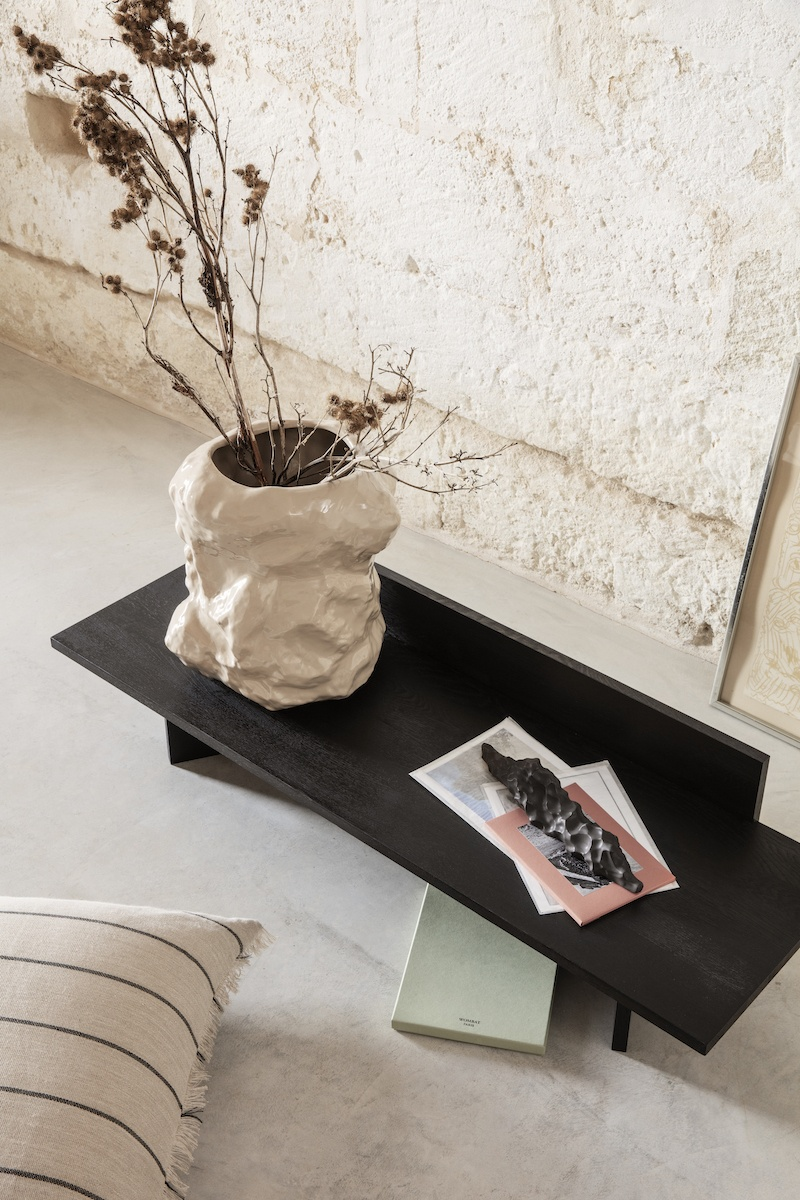 Tuck Vase von fermLIVING in Beige auf einem niedrigen Beistelltisch, vor einer Sandsteinwand