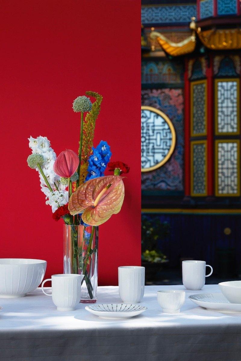 Window Vase von Tivoli Normann Copenhagen auf einer Kaffeetafel, Hintergrund halb rote Stellwand, andere Häfte ein asiatisch wirkender Pavillon.