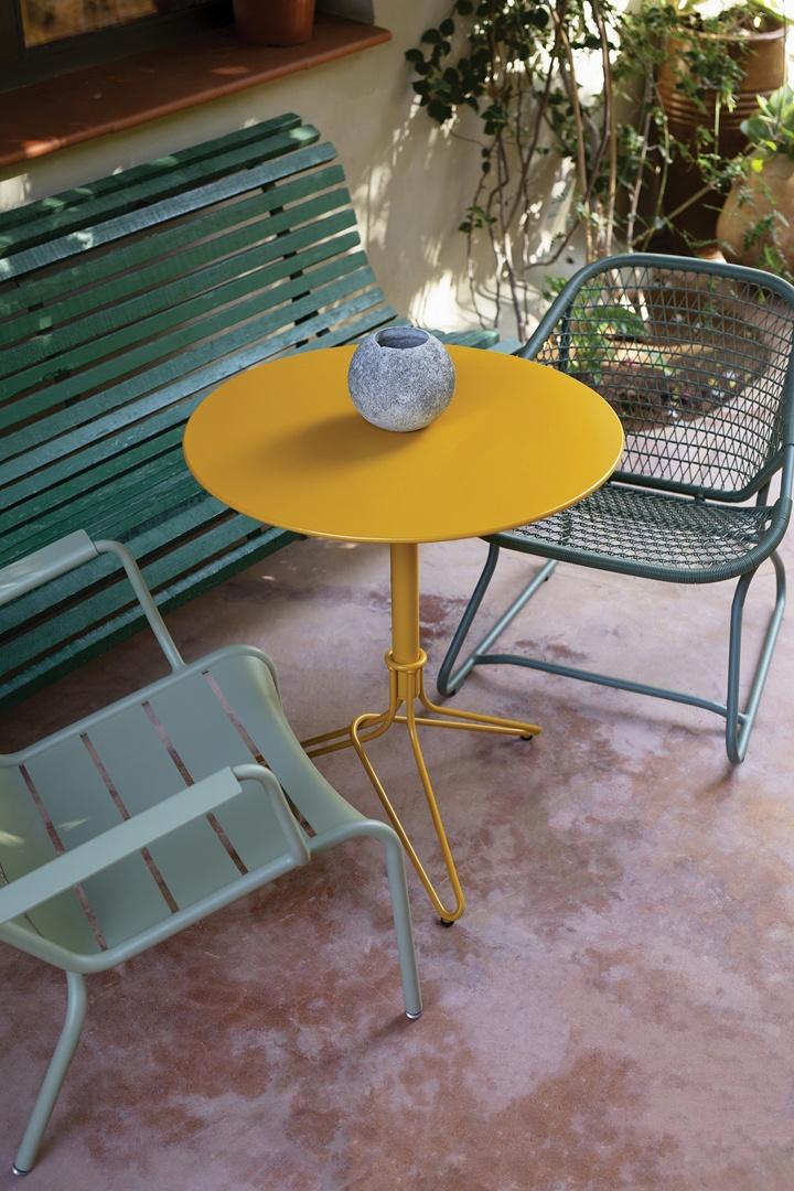 Mix aus grüner Holzbank, Stuhl und Sessel aus Metall und gelbem Tisch in der Mitte, auf einer Terrasse.