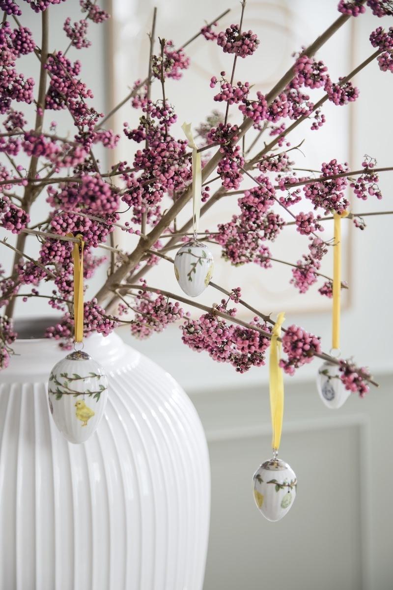 Osterstrauß mit pinken Beeren und Porzellaneiern an gelben Bändern, in einer weißen Blumenvase.