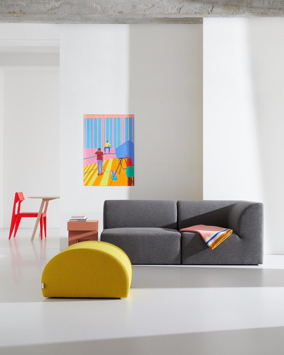 SELECTED Objekte unserer Tage - Set up aus MEYER Sofa in Grau, davor ein gelber LEVI Pouf. Im Hintergrund ein SCHULZ Stuhl in Leuchtrot.