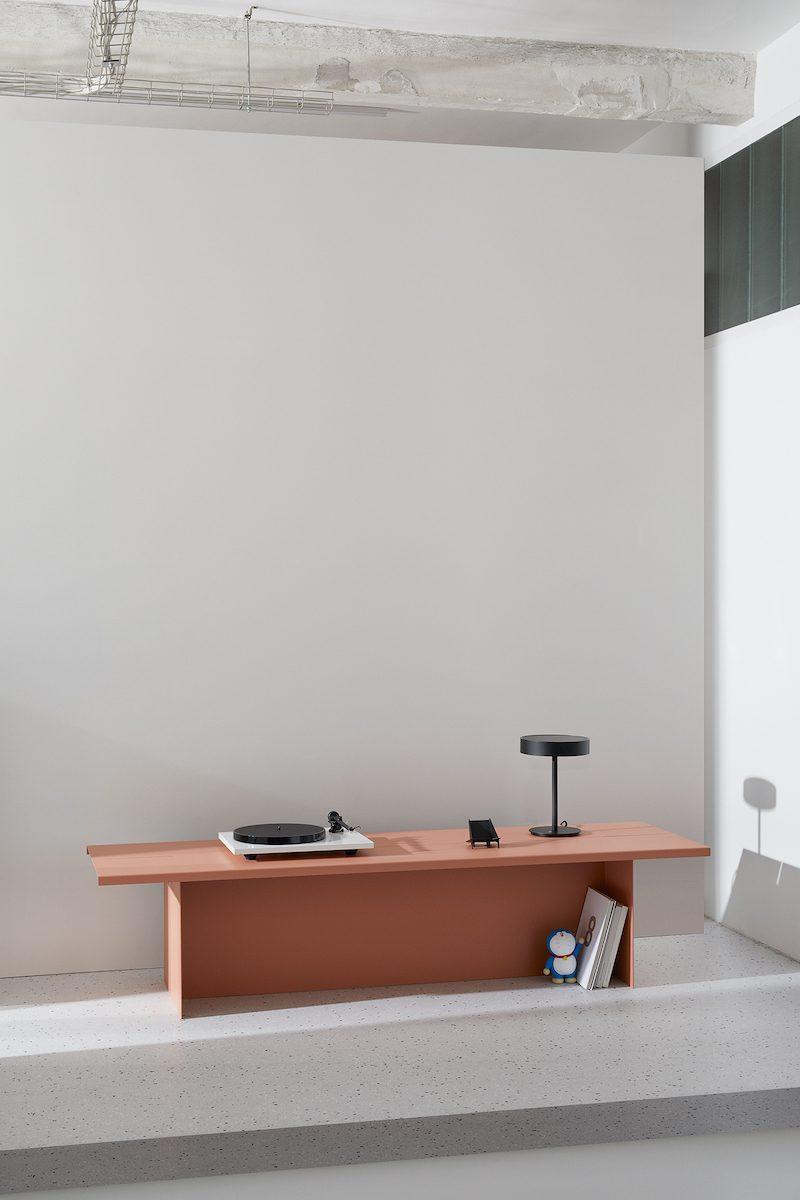 ZEBE Bank in Aprikosa vor einer weißen Wand. Darauf stehen ein Plattenspieler und eine schwarze Tischleuchte.