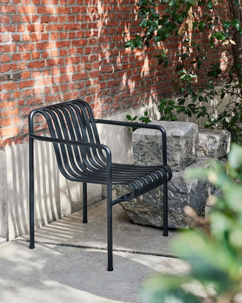 Schwarzer Palissade Sessel von HAY vor einer Ziegelmauer.