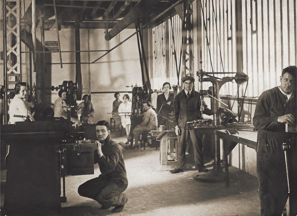 historisches Photo in das Atelier Ravel. Arbeiter_innen stehen und sitzen an ihren Werkplätzen.