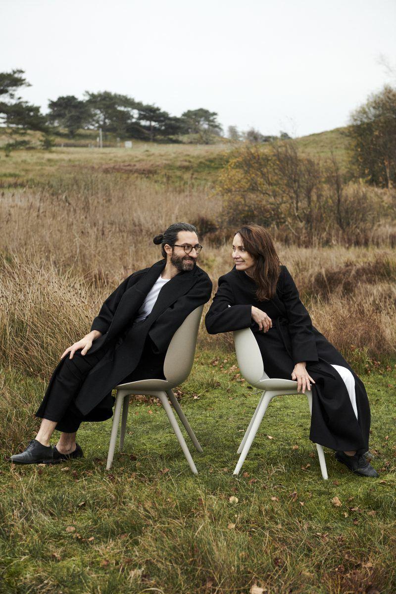 Portrait Duo GamFratesi auf einer Wiese, sitzen auf zwei Beetle Outdoor Chairs und schauen sich über die Schulter an.