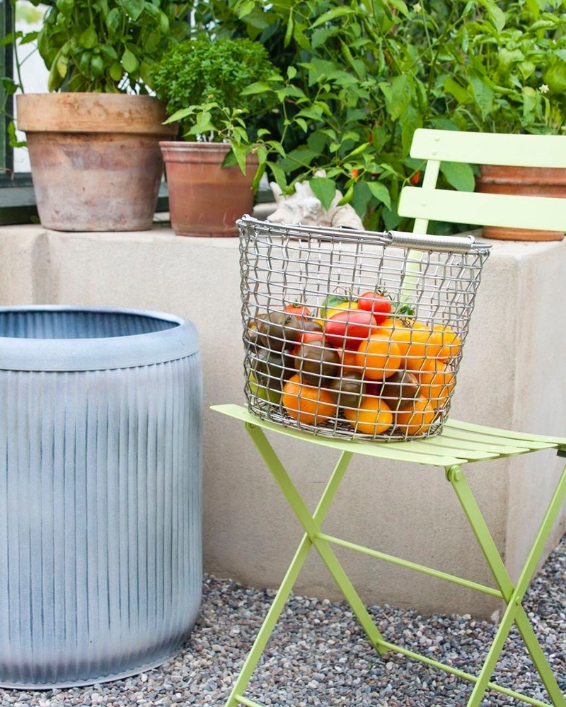 Korbo Korb halbvoll mit bunten Tomaten auf einem grünen Gartenklappstuhl