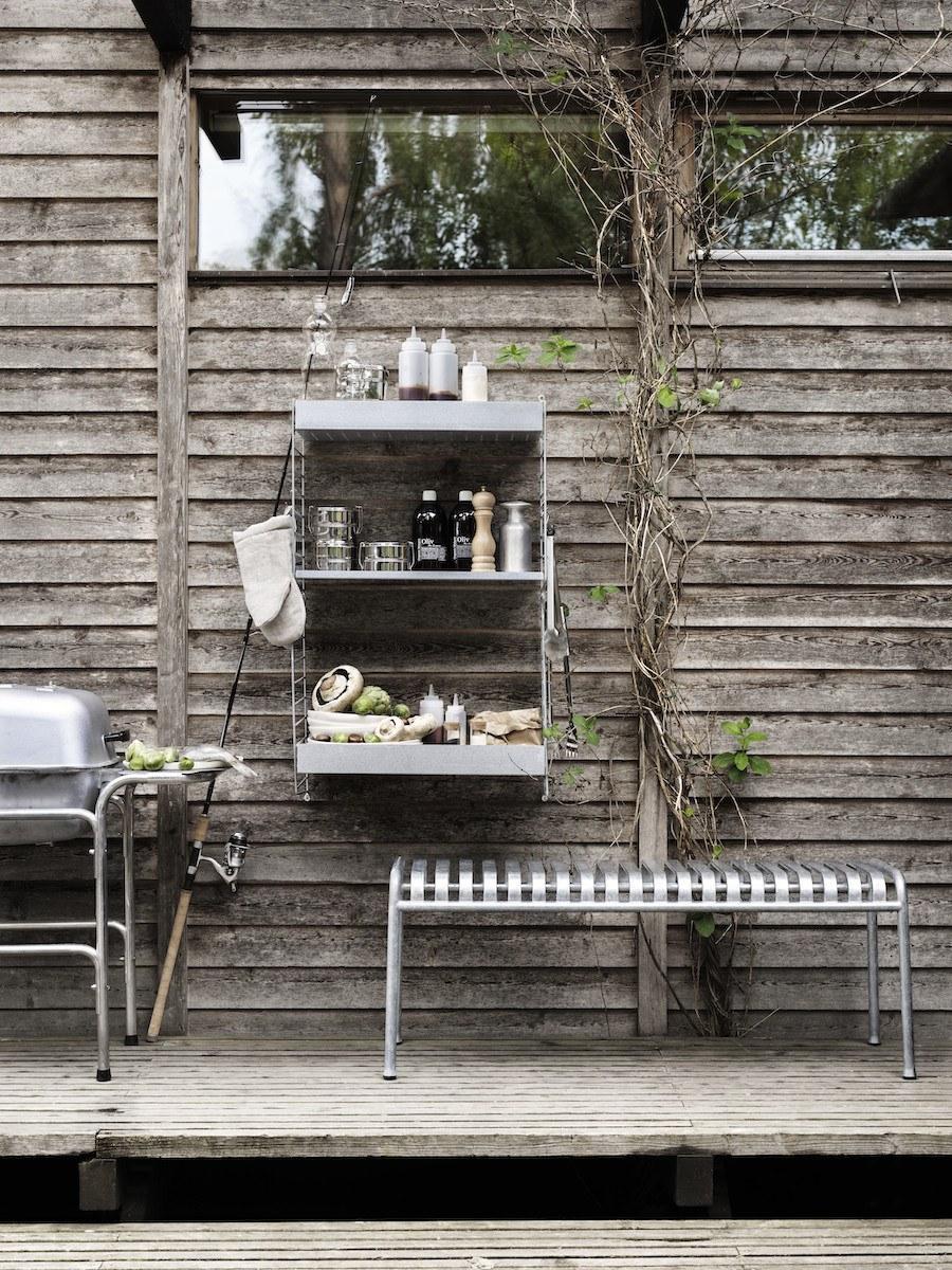 Outdoor Wandregal von String bestückt mit Kochutensilien und Zutaten, daneben ein Grill.