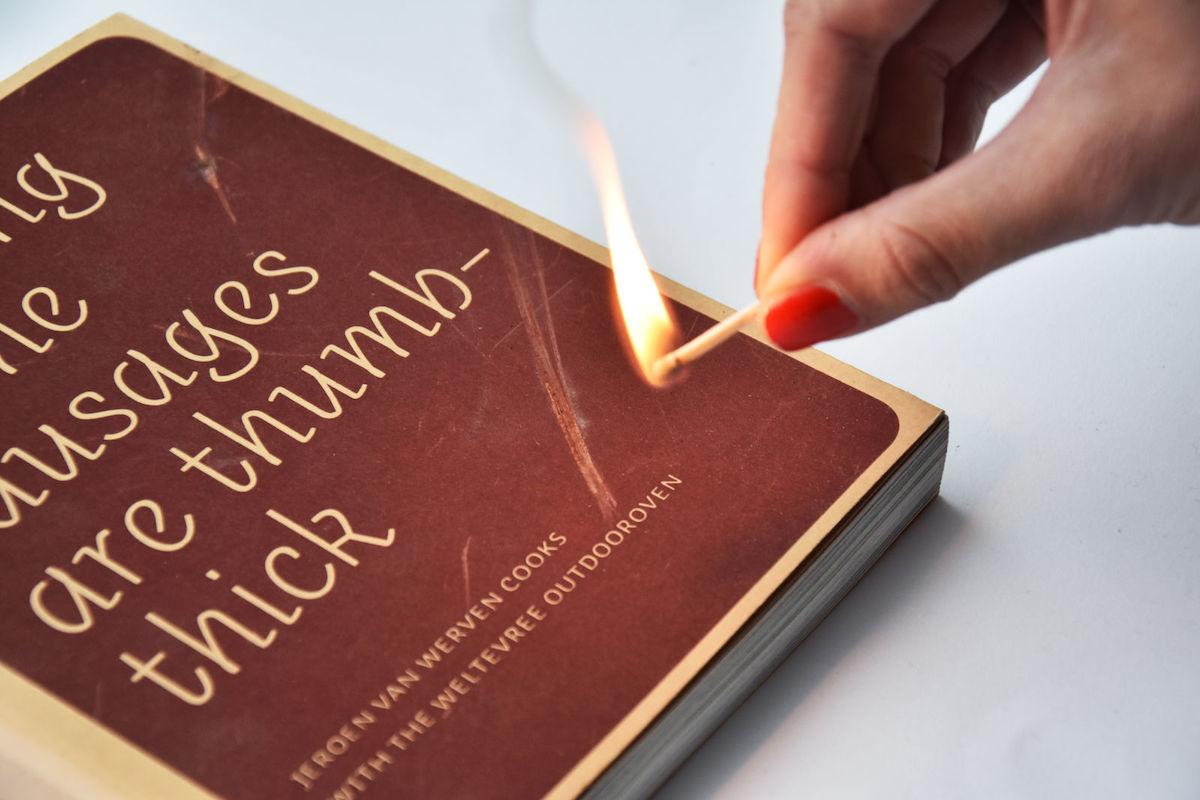 """Eine Hand hält das brennende Streichholz über das Kochbuch """"Daumendick müssen die Würstchen schon sein""""."""