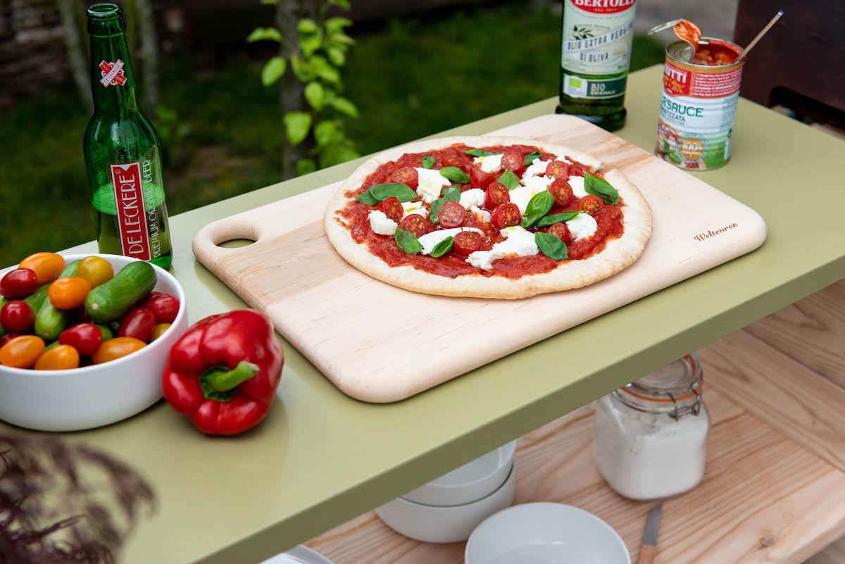 Outdoormood. Großes Holzbrett mit einer ungebackenen Pizza Mozzarella, daneben frische Zutaten und eine offene Flasche Bier.