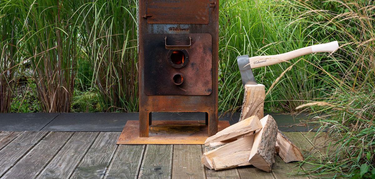 Eine Axt ist in einen Holzscheid eingeschlagen. Im Hintergrund steht der Outdooroven.